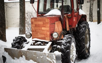Photo of a tractor with a scraper blade moving snow